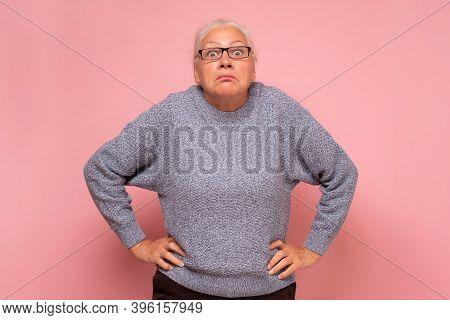 Senior Confused Woman In Glasses Shrugging Shoulders.