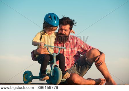 Father Teaching Son Riding Bike. Happy Dad Helping Excited Son To Ride A Bicycle. Trust And Support.