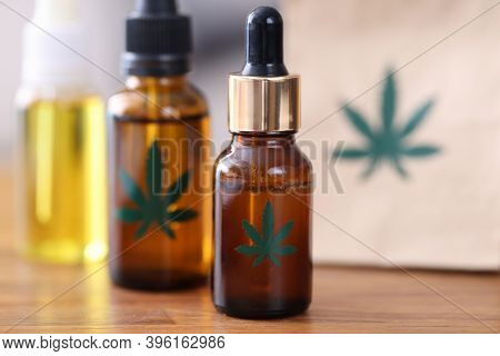 Jars With Marijuana Extract Standing On Wooden Table Close-up. Sale Of Narcotic Drugs Based On Hemp