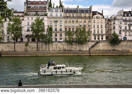Europe, Paris, May, 2015 - Seine River Embankment With Ancient Architecture And A Pleasure Ship In S