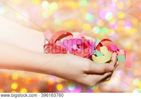 Childrens Hands Hold A Serpentine On A Blurry Bokeh Background. New Year, Christmas Mood