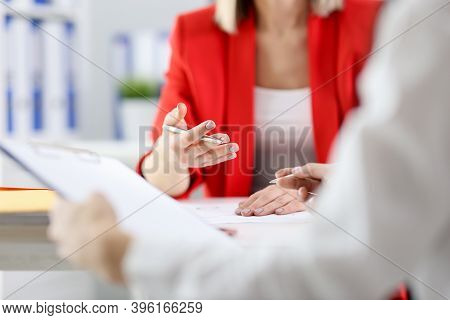 Businesswoman Holding Ballpoint Pen In Hands And Talking With Colleague In Office Closeup. Developme