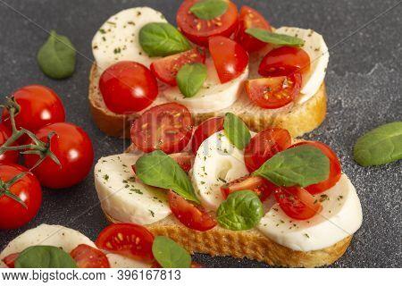 Caprese Bruschetta Toasts With Mozzarella, Cherry Tomatoes And Fresh Garden Basil.traditional Italia
