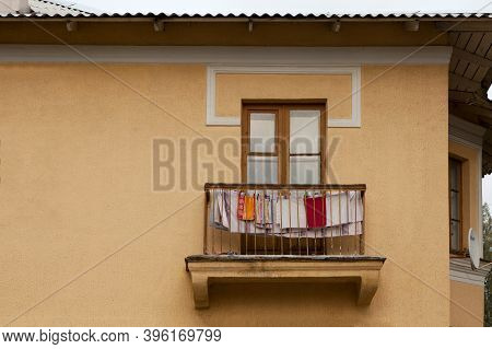 One Balcony In An Old Yellow Apartment Block. Linen And Towels Are Dried On The Balcony Of The House