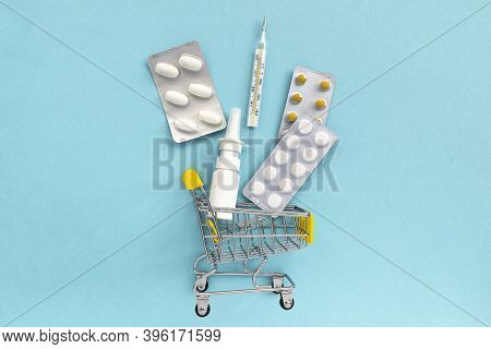 Shopping Grocery Cart With Medicament, Tablet, Spray, Thermometer On Blue Background. Concept Of Hea