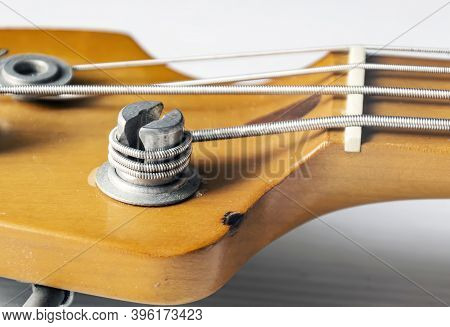 Detail Of A Tuning Post On The Wooden Headstock Of An Electric Bass Guitar. Musical Instruments And