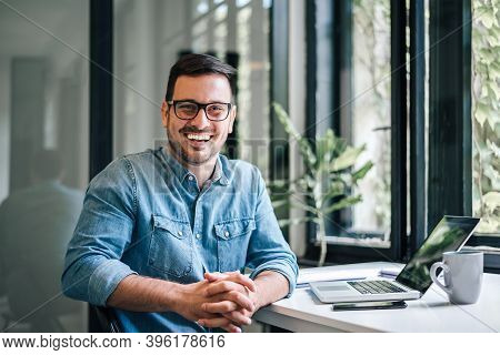 Portrait Of Young Smiling Happy Handsome Successful Businessman Entrepreneur Freelancer Working From