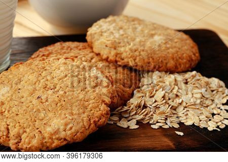 Oat Cookies And Oat Flakes On Wooden Surface