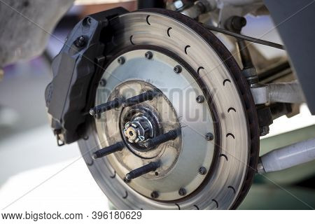 High Performance Brake Caliper On A Disc Brakes With Brake Pads Of A Car. No Tire.