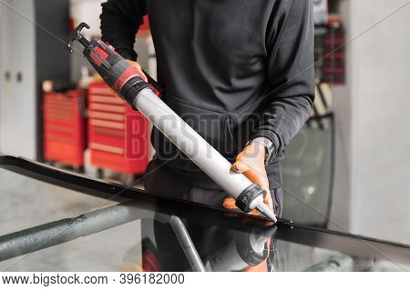 Glazier Applying Rubber Sealing To Windshield In Garage, Close Up. High Quality Photo