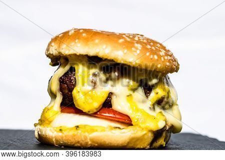 Tasty Homemade Cheeseburger Isolated On White Background. Beef Cheeseburger With Melting Cheese.