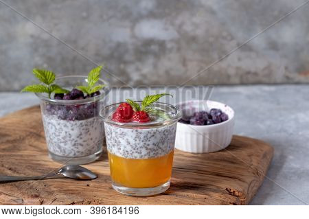 Dessert With Chia Seeds And Berries In Glass Glasses On A Wooden Board On A Gray Background. Superfo