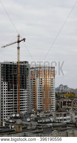Huge Unfinished Multistory Building With Crane Jib At Cloudy Sky Background. Cityscape With Rooftops