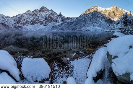 Winter In Mountains. Frozen Lake With Transparent Ice In Mountains. Alps Landscape.