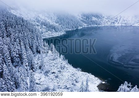 Winter Lake With Frosty Christmas Trees Covered With White Snow. Winter Christmas Background. Mounta