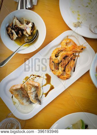Slices Of Fresh Healthy Fish With Shrimps, Salmon Steak A Octopus On A Plate On A Table. Fish Meze.