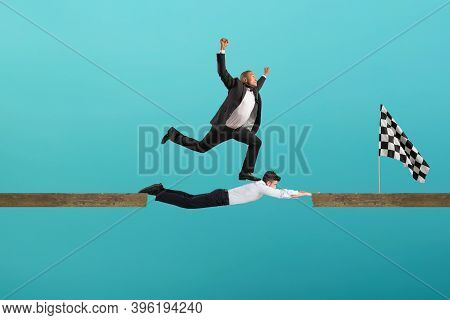 Businessman Uses His Body Like A Bridge To Help His Coullague To Reach The Flag. Concept Of Teamwork