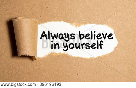 Text Always Believe In Yourself Appearing Behind Torn Brown Papertext Culture Appearing Behind Torn