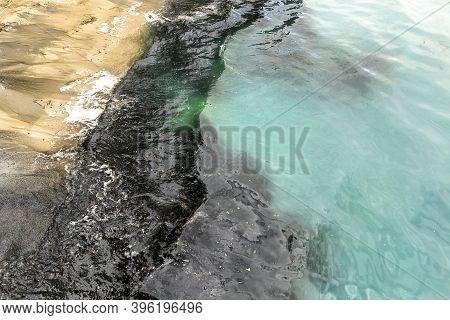 Beautiful Sand Sea Blue Water Or Lake Beach Polluted With Black Harmful Toxic Sewage Chemicals. Natu
