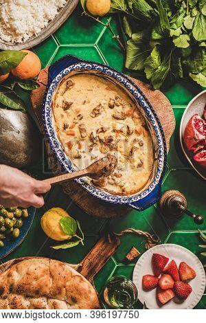 Turkish Style Family Dinner. Flat-lay Of Female Hands Stirring Turkish Lamb In Yogurt Sauce Over Tab