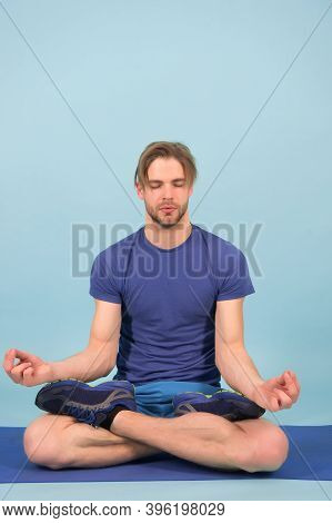Man Meditate On Yoga Mat. Sportsman Relax In Lotus Pose. Fashion Athlete Practice Yoga In Gym. Medit