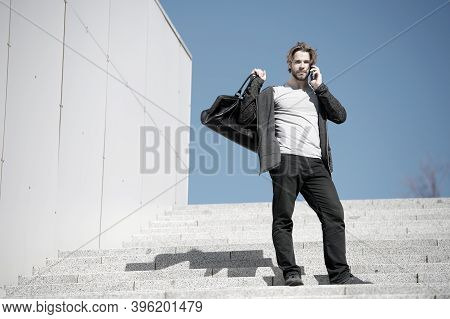 Guy Talk On Mobile Phone At Stair On Blue Sky. Man With Bag, Smartphone On Steps On Sunny Day. Vacat