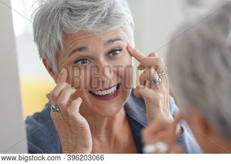 Mature white-haired woman checking eye wrinkles in front of mirror