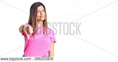 Beautiful caucasian woman wearing casual clothes looking unhappy and angry showing rejection and negative with thumbs down gesture. bad expression.