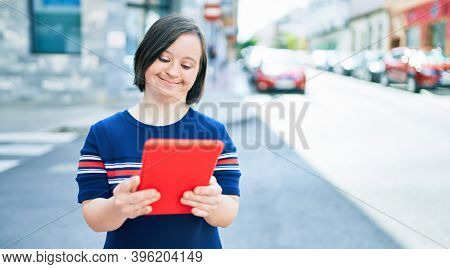Beautiful brunette woman with down syndrome at the town on a sunny day using touchpad device