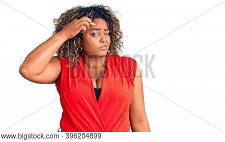 Young african american plus size woman wearing casual style with sleeveless shirt pointing unhappy to pimple on forehead, ugly infection of blackhead. acne and skin problem
