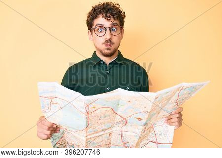 Young caucasian man with curly hair holding city map puffing cheeks with funny face. mouth inflated with air, catching air.