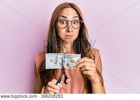 Young brunette woman cutting dollars with scissors for currency devaluation puffing cheeks with funny face. mouth inflated with air, catching air.