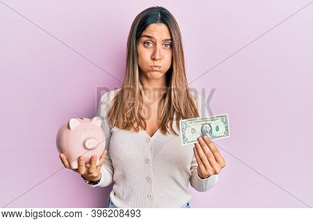 Brunette young woman holding one dollar banknote and piggy bank puffing cheeks with funny face. mouth inflated with air, catching air.