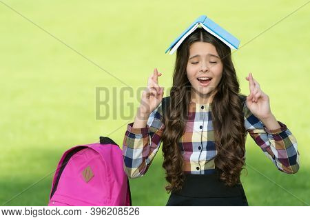 I Dont Want To Jinx It. Superstitious Child Make Wish Holding Book On Head. Victim Of Superstition.