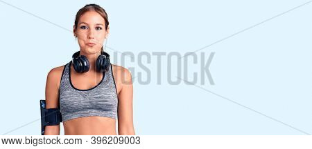 Young beautiful hispanic woman wearing gym clothes and using headphones puffing cheeks with funny face. mouth inflated with air, crazy expression.