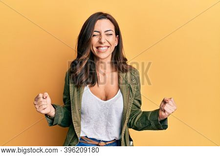 Young brunette woman wearing casual clothes over yellow background very happy and excited doing winner gesture with arms raised, smiling and screaming for success. celebration concept.