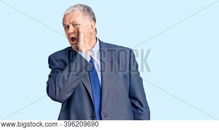 Senior grey-haired man wearing business jacket hand on mouth telling secret rumor, whispering malicious talk conversation