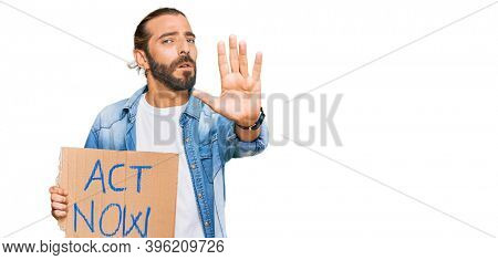 Attractive man with long hair and beard holding act now banner with open hand doing stop sign with serious and confident expression, defense gesture