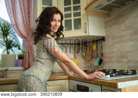 Beautiful sexy brunette woman housewife iat home in the interior in the kitchen