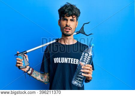 Young hispanic man holding plastic bottle and litter picker to recycle in shock face, looking skeptical and sarcastic, surprised with open mouth