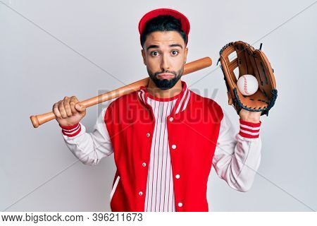 Young man with beard playing baseball holding bat and ball puffing cheeks with funny face. mouth inflated with air, catching air.