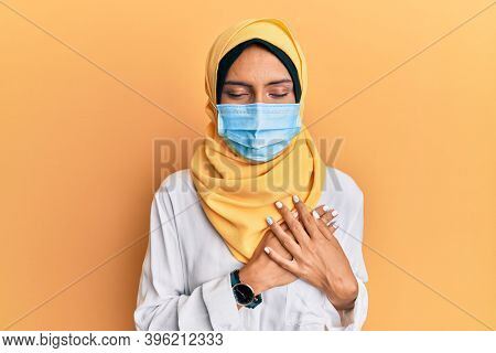 Young brunette arab woman wearing traditional islamic hijab and medical mask smiling with hands on chest with closed eyes and grateful gesture on face. health concept.