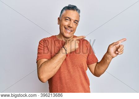 Handsome middle age mature man wearing casual clothes smiling and looking at the camera pointing with two hands and fingers to the side.