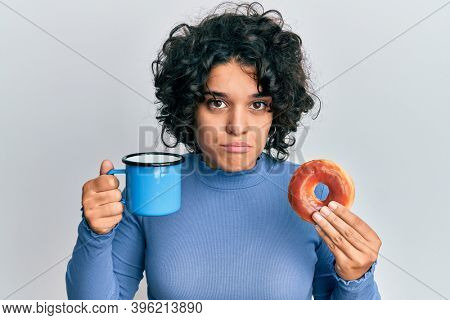Hispanic woman with curly hair eating doughnut and drinking coffee puffing cheeks with funny face. mouth inflated with air, catching air.
