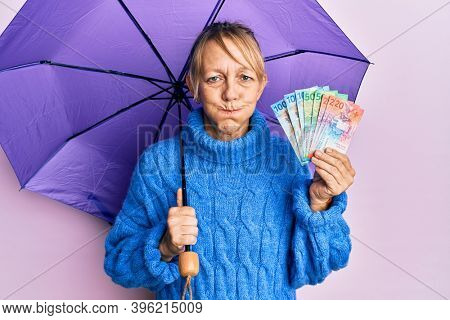 Middle age blonde woman holding umbrella and swiss franc banknotes puffing cheeks with funny face. mouth inflated with air, catching air.