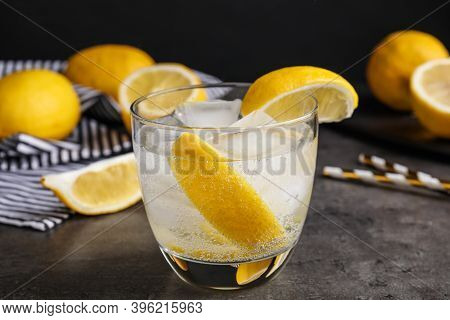 Soda Water With Lemon Slices And Ice Cubes On Grey Table