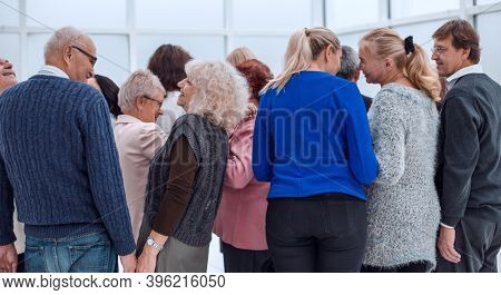 a group of old people standing with their backs indoors