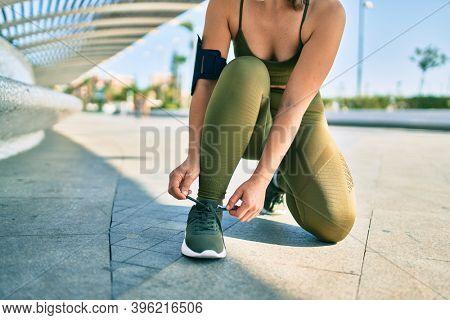 Sportswoman wearing sportswear tying her shoelaces at the city