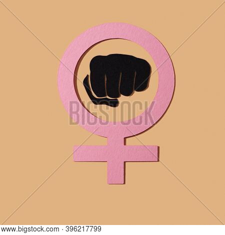 the women power symbol, a raised fist in a female gender symbol, made with cutouts of paper of different colors on a salmon pink background
