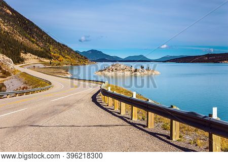 Asphalt highway leads to Abraham Lake. Magnificent Indian summer in the Canadian Rockies. The  Rocky Mountains, Canada